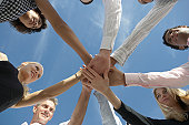 Group of people holding hands in circle, low angle view