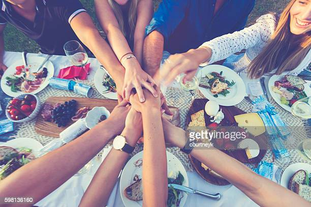 Group of people holding hands over dinner.