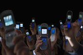 Group of people holding open cell phones up in air