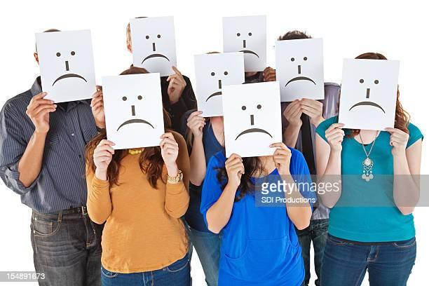 Grupo de personas de retención de las señales hasta la triste cara