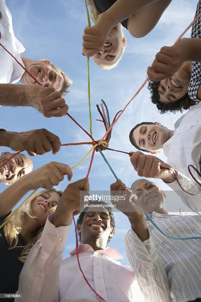 Group of people holding string tied together, smiling, low angle view