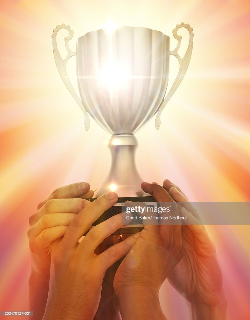 Group of people holding trophy, close-up of hands : Stock Photo