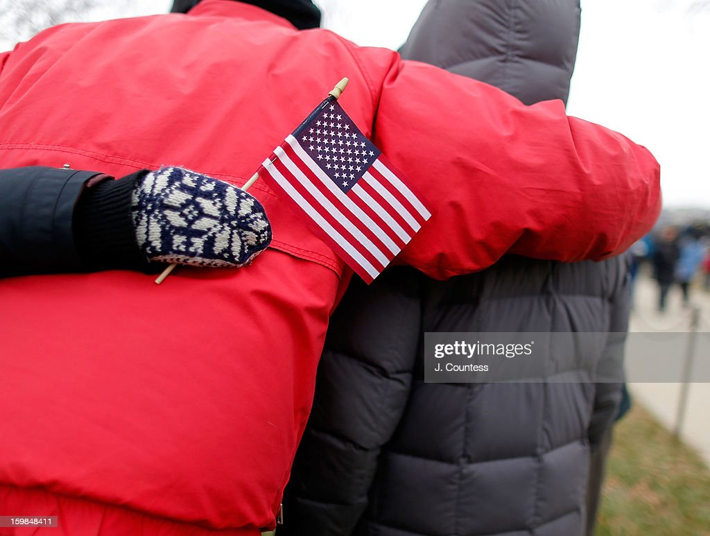 A group of people hug at the base of the Washington Monument on the National Mall where thousands of spectators watched the 57th United States Presidential Inauguration ceremony on January 21, 2013 in Washington, DC.