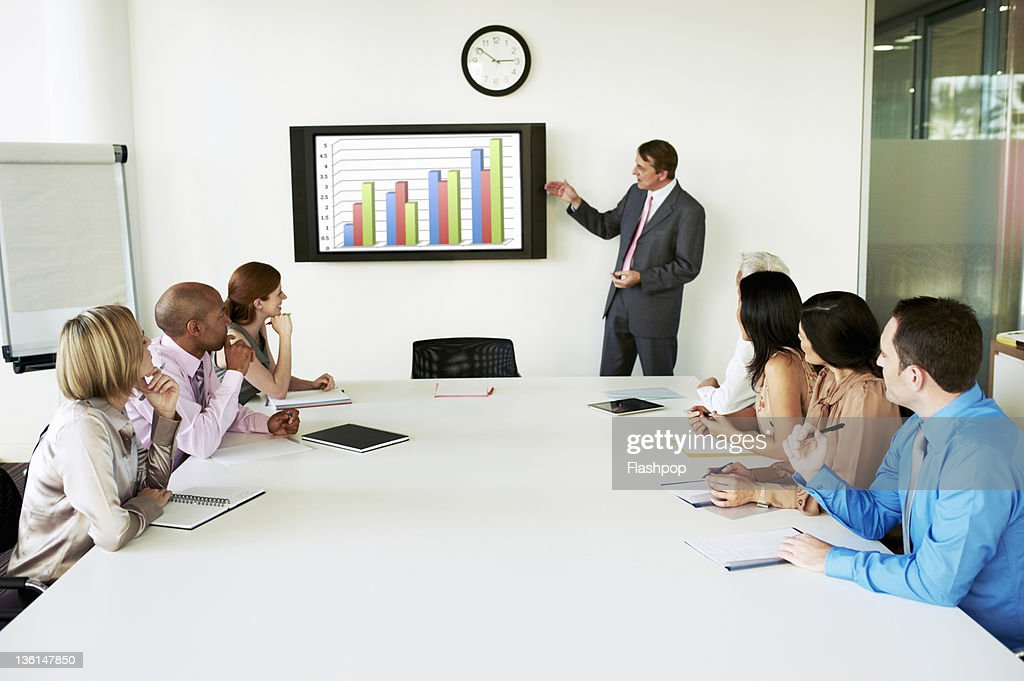 Group of people in a meeting looking at graph : Stock Photo