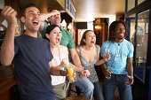 Group of people in bar, cheering