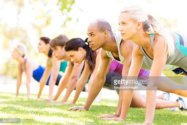Group Of People In Bootcamp Workout Class Doing Pushups