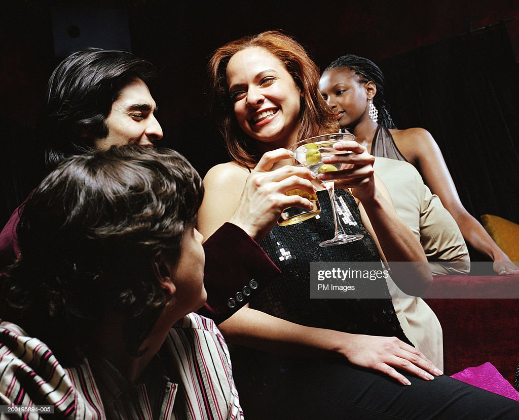 Group of people in lounge woman and man toasting, smiling : Stock Photo
