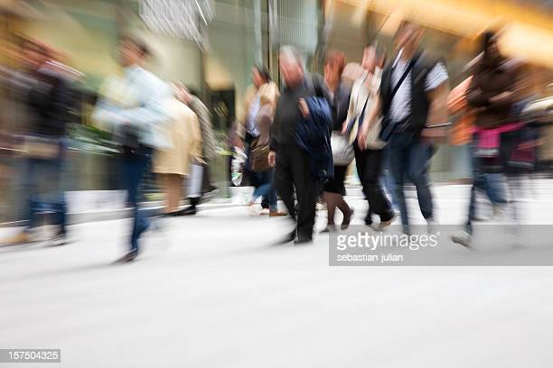 A group of people in motion depicting a typical day in city