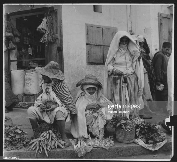 A group of people in native dress sell vegetables on the pedestrian walkway