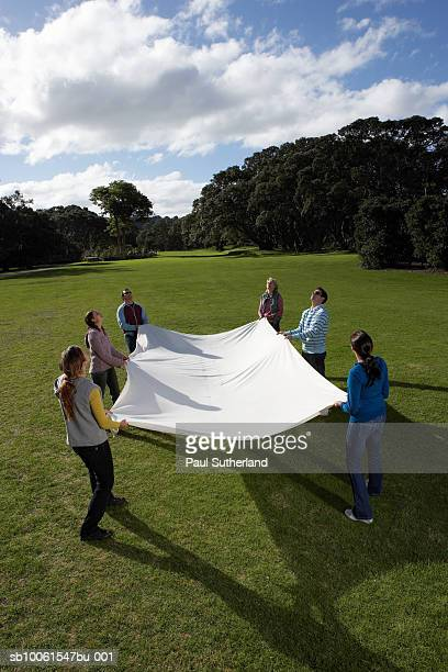 Group of people in park holding large white sheet