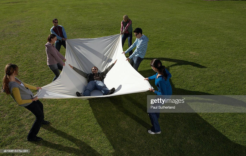 Group of people in park holding large white sheet with man lying inside