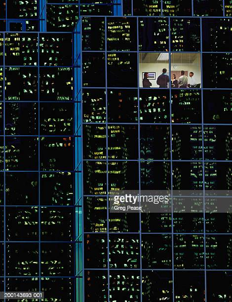 Group of people in room of office building, night (Digital composite)