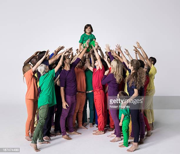 Group of people in studio lifting a child