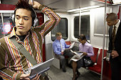 Group of people in subway train, focus on young man wearing headphones holding laptop