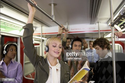 Group of people in subway train, young woman wearing headphones reading book in foreground