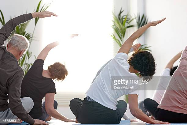 Group of people in the gym doing stretching exercise