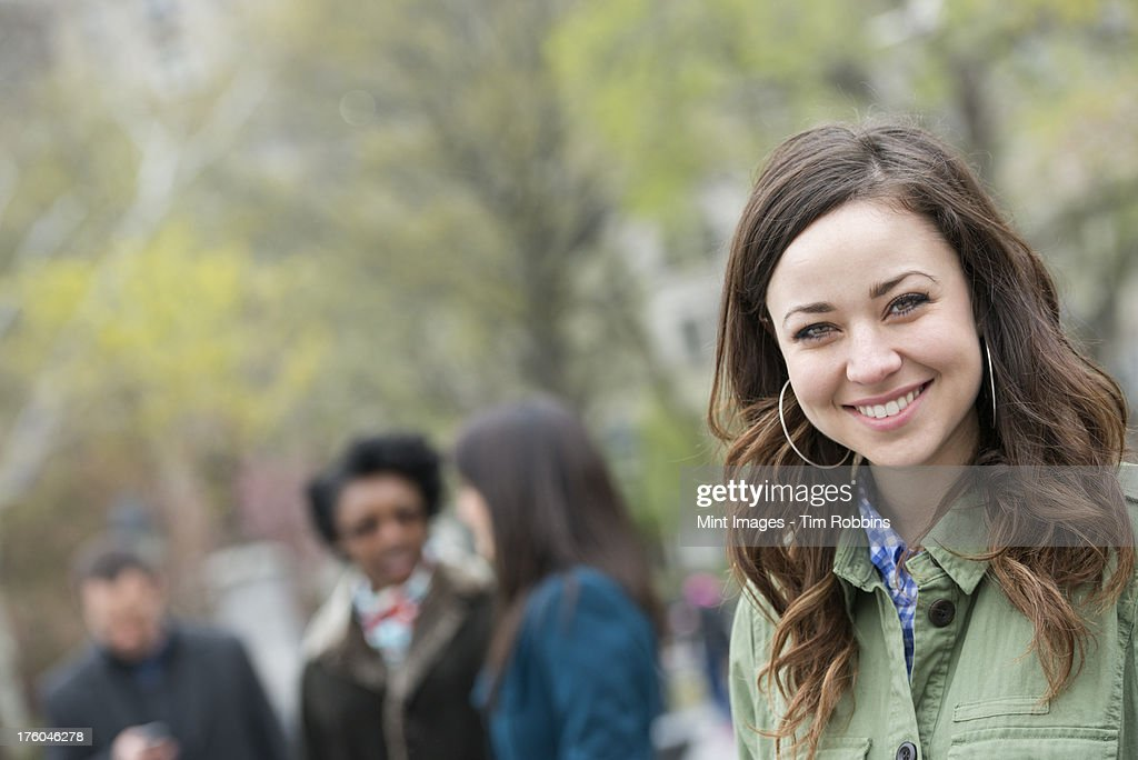A group of people in the park. A young woman in an open necked shirt, smiling and looking at the camera. : Stock Photo