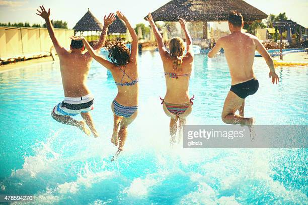 Group of people juming in swimming pool.