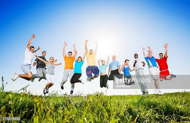 Gruppe von Menschen springen in Feld.