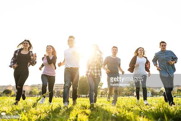 Eine Gruppe von Menschen springen im Park in der Dämmerung