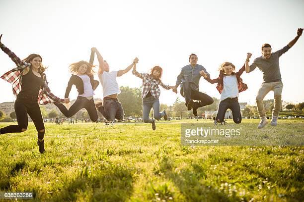 Grupo de personas salto en el parque al atardecer