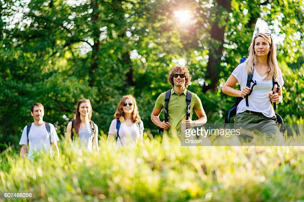 Group of people lead by woman hiking in woods