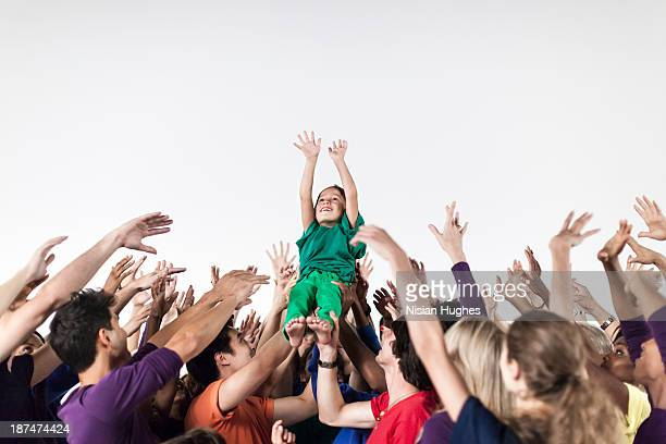 Group of People Lifting a Child in Celebration