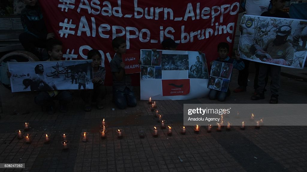 A group of people light candles for the victims of air strikes conducted by the Assad regime and Russia over the Aleppo in Idlib, Syria on May 4, 2016.