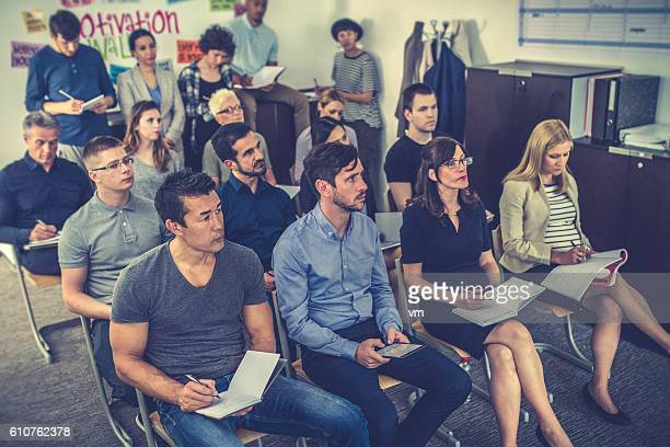 Group of people listening and taking notes on a seminar