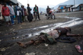 A group of people look at the body of a dead civilian in Sake in the east of the Democratic Republic of the Congo on November 23 2012 Heavy fighting...