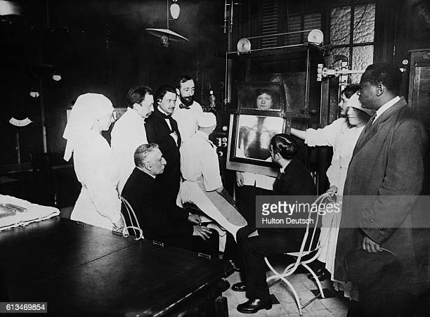 A group of people look at the xray photograph of a woman's rib cage as ahe stands behind the xray equipment