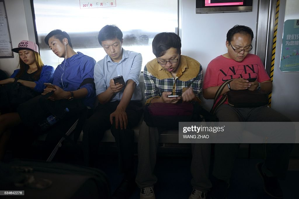 A group of people look at their mobile phone while commuting on the subway in Beijing on May 27, 2016. / AFP / WANG