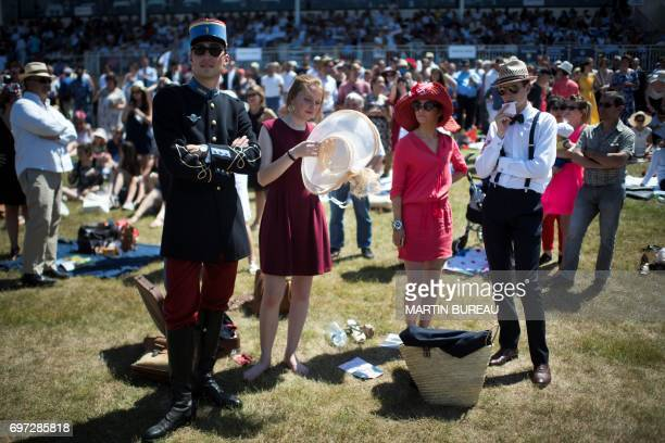 TOPSHOT A group of people look on as they enjoy the sunny weather prior to the start of the Prix de Diane a 2100meters flat horse race on June 18...