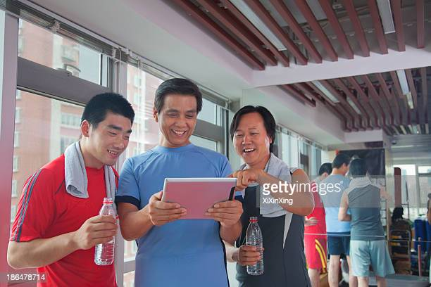 group of people looking at digital tablet in the gym