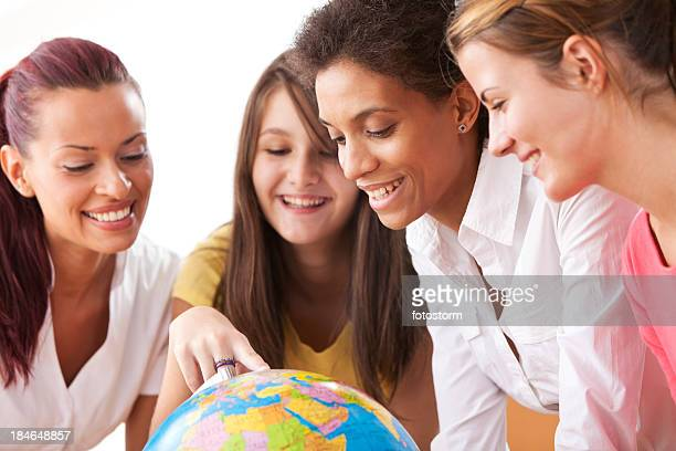Group Of People Looking At Globe In The Classroom