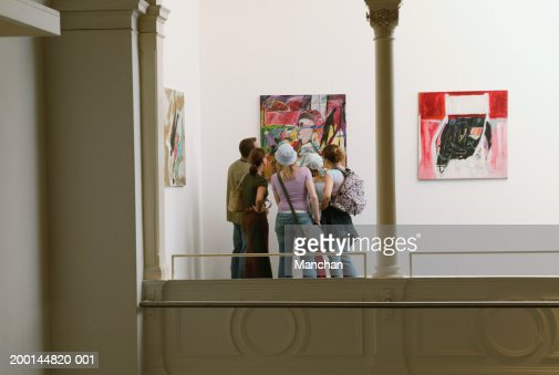 Group of people looking at painting in gallery, rear view : Stock Photo