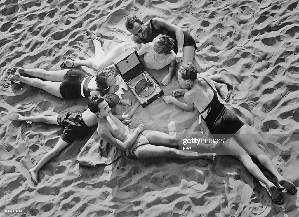 A group of people lying on a sandy beach and listening to records on a wind-up gramophone, circa 1930.