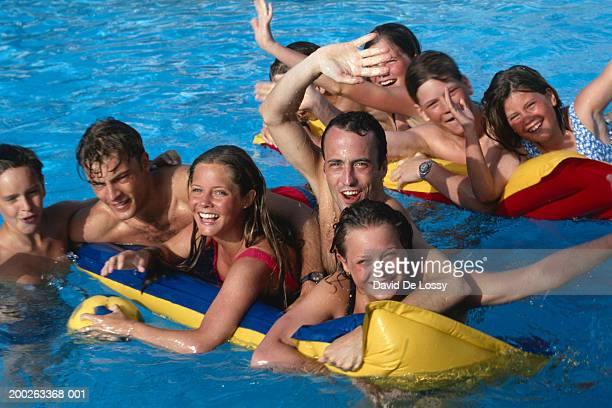 Group of people lying on air bed in swimming pool