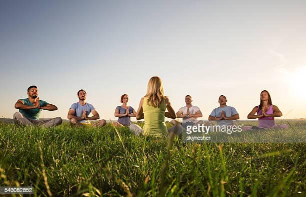 Groupe de personnes en cours de yoga méditation au coucher de soleil.