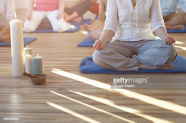 Group of people meditating, low section.