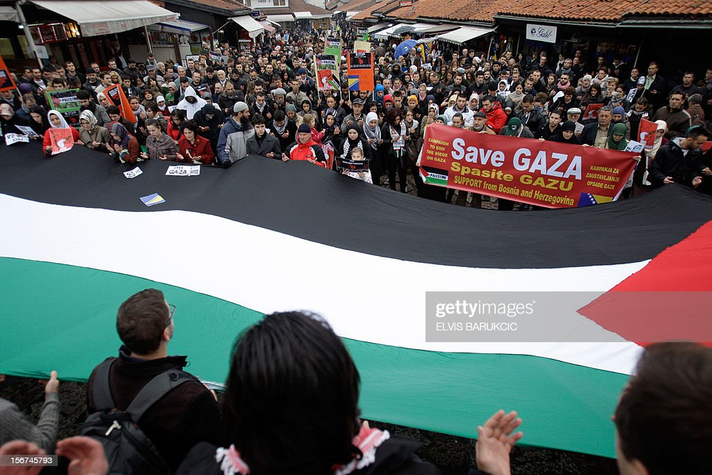 A group of people of Palestinian origin, backed by several hundred citizens of Sarajevo, hold a giant Palestinian flag as they walk on November 20, 2012 through the city center, in support of the Palestinian people after the latest Israeli attacks in Gaza. A larger protest has been anounced for November 23. AFP PHOTO / ELVIS BARUKCIC