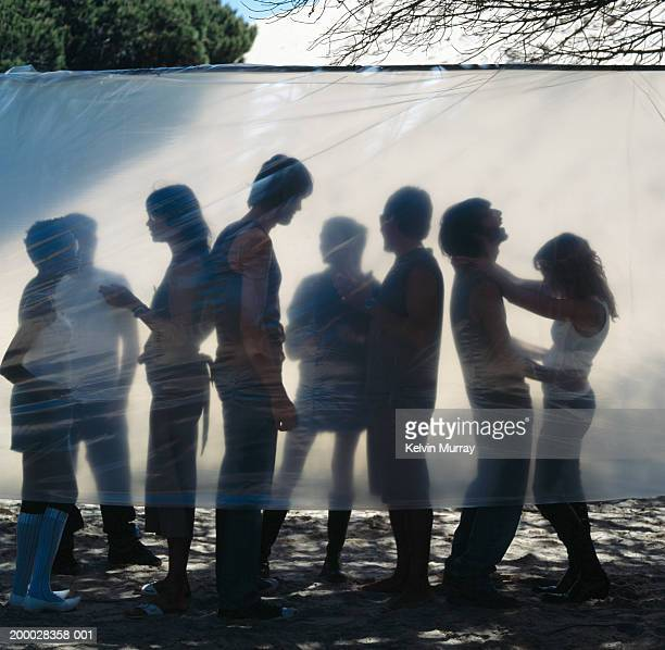 Group of people on beach behind plastic sheet