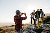 Young man taking picture of his friends while trekking in countryside during summer vacation. Group of people on hiking taking photographs with mobile phone.
