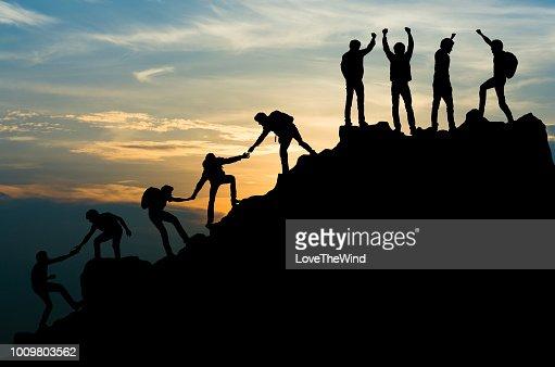 Group of people on peak mountain climbing helping team work , travel trekking success business concept : Stock Photo