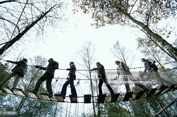 Group of people on rope bridge, low angle view