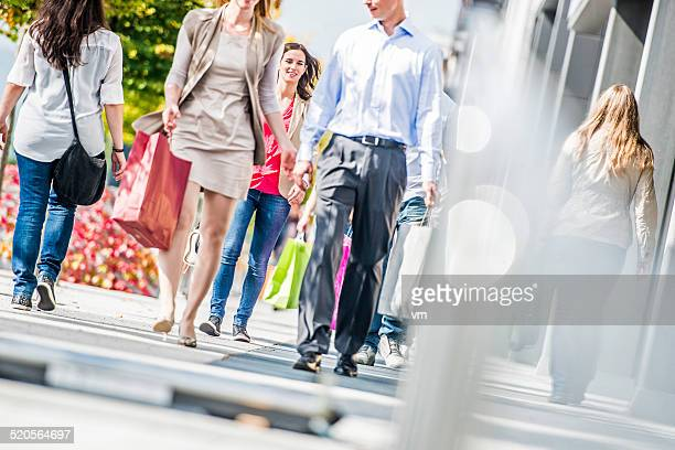 Group of People on Sidewalk with Shopping Bags
