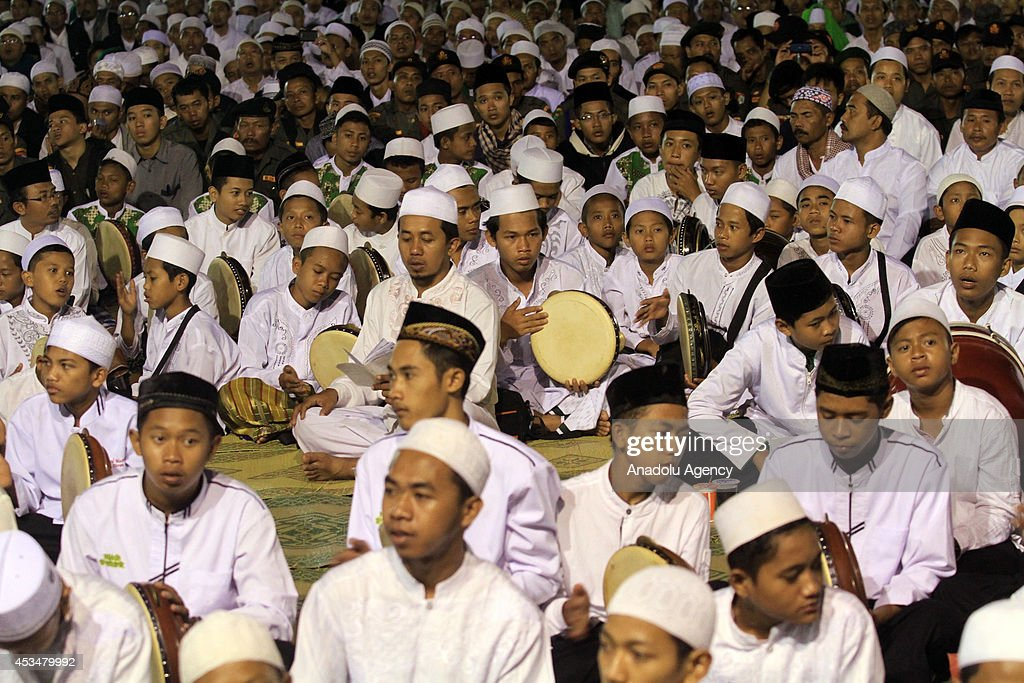 A group of people play frame drums and perform hymn as more than 50,000 Indonesian Muslims gathered in Solo, to protest against the attacks of the Islamic state in Iraq and Syria (ISIS) , on August 10, 2014 in Solo, Central Java, Indonesia.