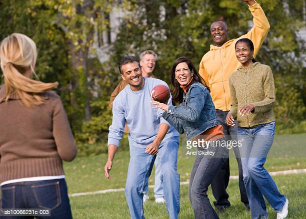 Group of people playing American football in park, smiling