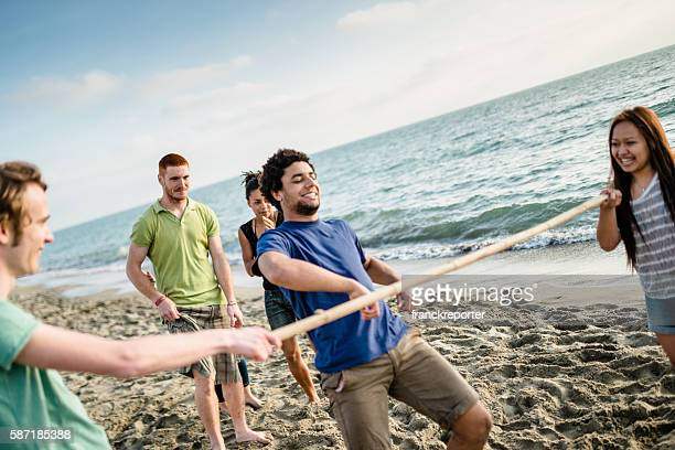 group of people playing limbo on the beach
