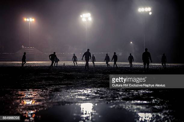 Group of people playing rugby on floodlit pitch at night